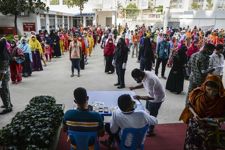 Labourers wait in line to collect their salary in a garment factory in Savar on the outskirts of Dhaka on April 7, 2020.