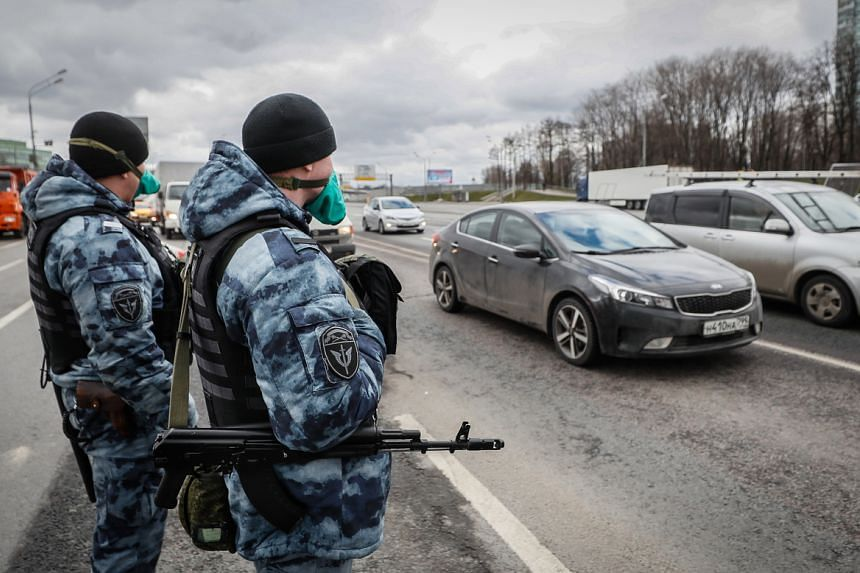 Police officers check identity cards and passes of people in vehicles entering Moscow on April 15, 2020.