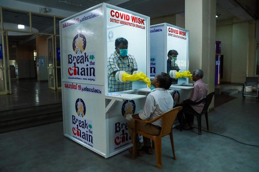 Medical staff collect samples from people at a Walk-In Sample Kiosk to test for the coronavirus in Kerala, on April 6, 2020.