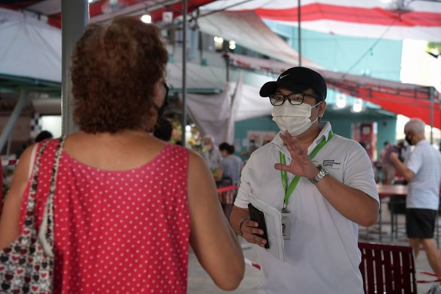 An enforcement officer from the National Environment Agency speaks to a resident at the Toa Payoh West Market and Food Centre on April 14, 2020.