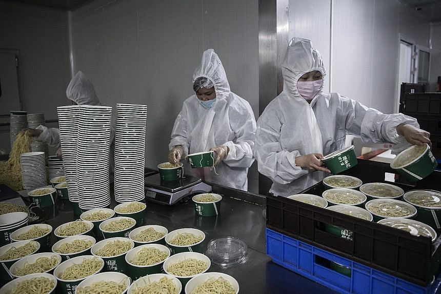 Workers wearing protective gear at a noodle factory in Wuhan, Hubei province. China's growth this year is set to stumble to 2.5 per cent, its slowest annual pace in nearly half a century, according to a Reuters poll.
