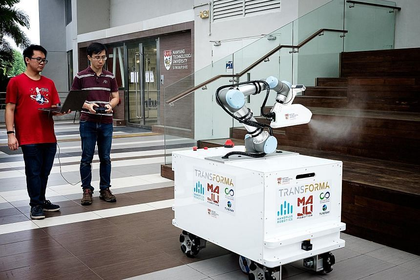 Mr Chong Zheng Hao (left) and Dr Quek Zhan Fan with the eXtreme Disinfection roBot, or XDBot. They are part of the Nanyang Technological University team that designed and built the robot in six weeks. The machine can disinfect large surfaces quickly,