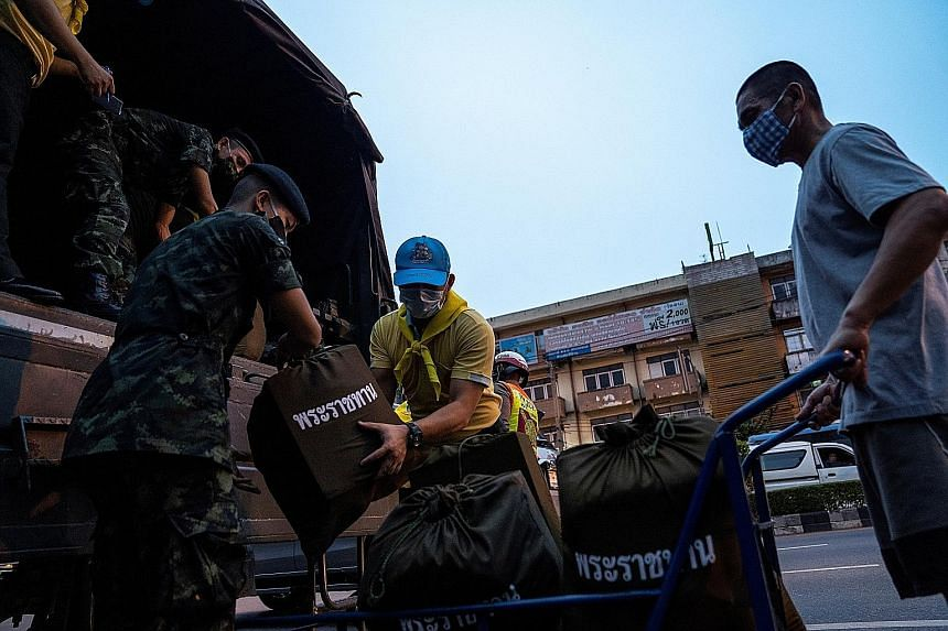 Soldiers and volunteers unloading provisions this week from Thailand's King Maha Vajiralongkorn and Queen Suthida for distribution to people amid the coronavirus pandemic.