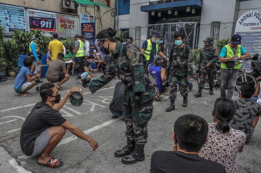 Members of the public, detained for roaming the streets, have their temperatures checked outside a police station in Quezon City, in Manila. PHOTO: AGENCE FRANCE-PRESSE