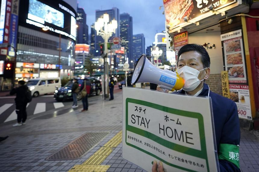 A metropolitan government employee urges passers-by to stay home in Tokyo on April 17, 2020.