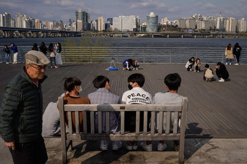 People relax at a park in Seoul on April 12, 2020.