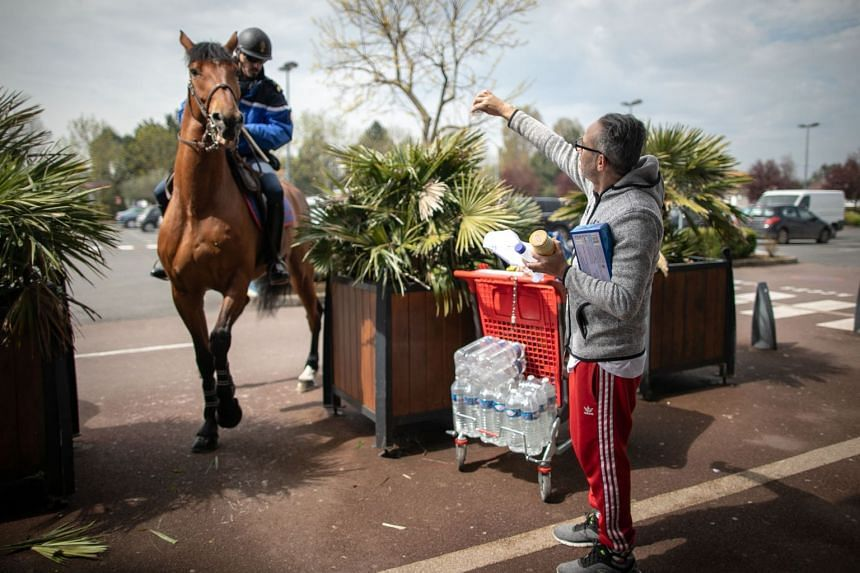 Mounted French gendarmes check people's mobility documents in Courseulles-sur-Mer, Normandy, April 17, 2020.
