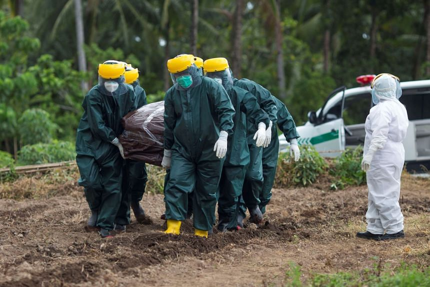 Municipality workers bury a coronavirus victim at a cemetery area in Sangihe Island, North Sulawesi.