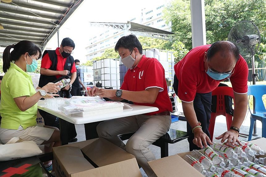 NTUC secretary-general Ng Chee Meng helping to prepare care packs for migrant workers in factory-converted dormitories yesterday.