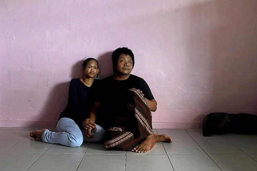 Sam (not his real name) and his wife in their two-room rental flat in Ang Mo Kio.