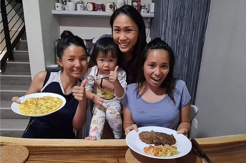 Fund manager Henrietta Yap, holding her daughter Beth, with her domestic helpers Kay Thi Khaing (left) and Alena Pacardo Palencia (right). With the circuit breaker in place, Ms Yap makes an effort to pitch in more at home. On Friday, she let her help