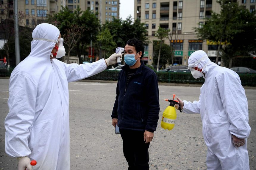 A factory employee is disinfected and his temperature taken by security guards in Wenzhou, China, on Feb 27, 2020.