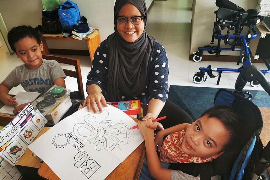 Madam Nur Hidayah Shahrudin helping her seven-year-old twins, Qays and Rizq (far right), with home-based learning. She also does daily therapy exercises with Rizq, who has cerebral palsy.