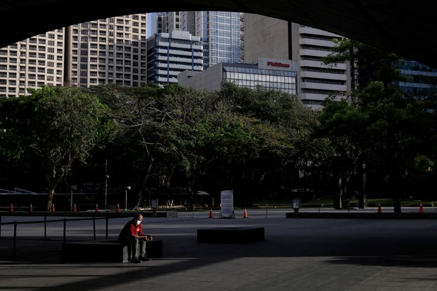 In a photo from March 17, 2020, a man wearing a protective mask sits outside the Philippine Stock Exchange in Manila.