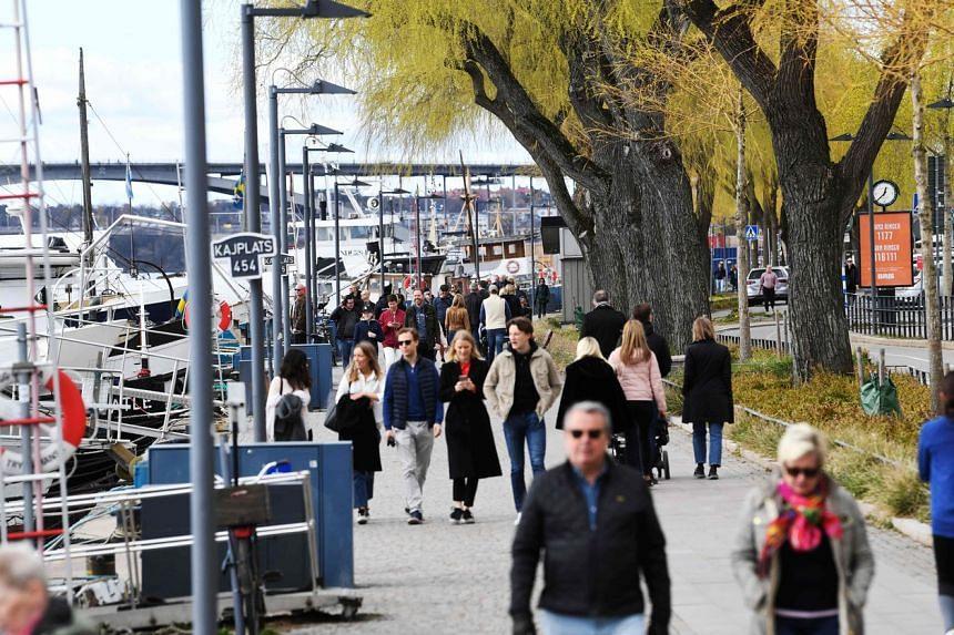People take a stroll at Norr Mälarstrand street in Stockholm on April 19, 2020.