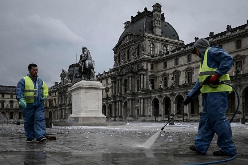 Workers clean the area in front of the Louvre Pyramid in Paris.