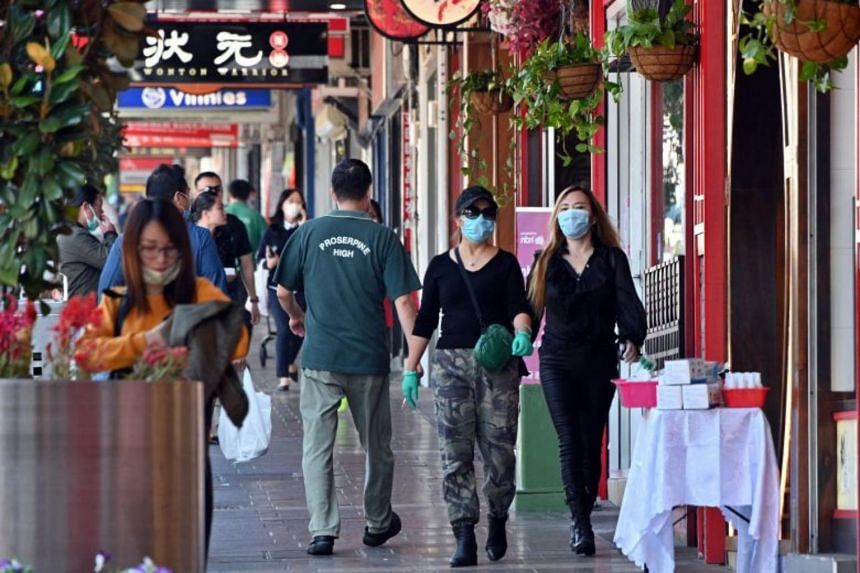 People wearing face masks walk in the Burwood suburb of Sydney, on April 14, 2020.