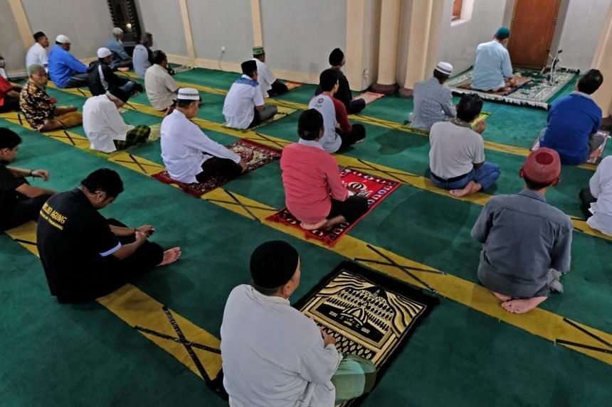 Muslims pray while practicing social distancing inside a mosque in Temanggung, Central Java province, Indonesia, on April 3, 2020.