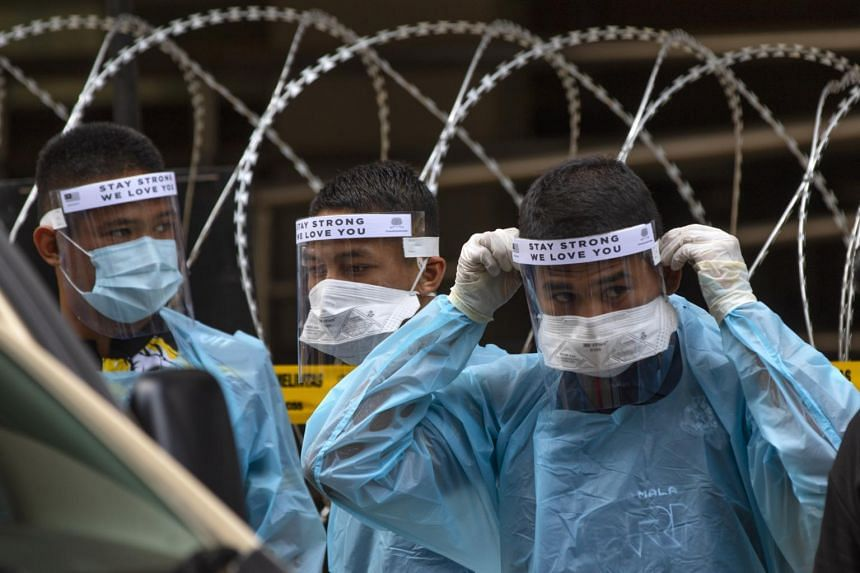 Malaysian health workers wearing protective suits and shields prepare to carry out Covid-19 tests in Kuala Lumpur, on April 15, 2020.