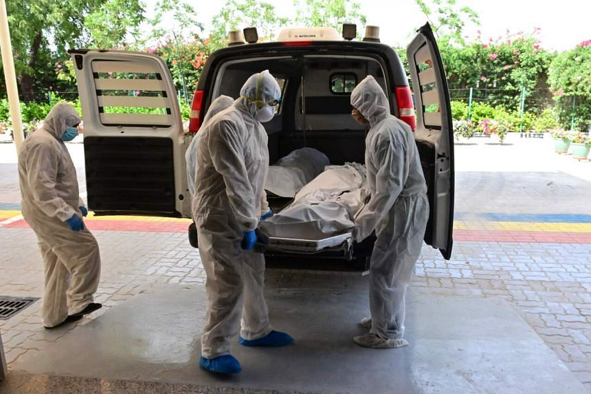 Employees transport the body of a Covid-19 victim to be cremated at a crematorium in Dubai on April 19, 2020.