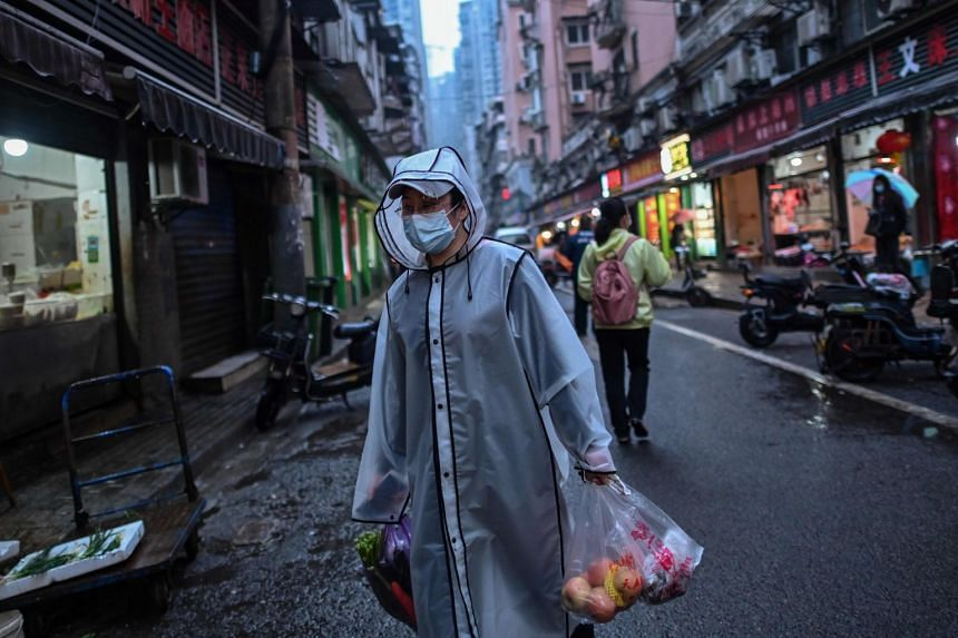 A person wearing a face mask carries groceries in a neighbourhood in Wuhan in China's central Hubei province, April 20, 2020.