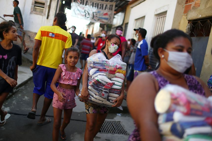 People wait in line to receive aid for poor families at the Mandela slum in Rio de Janeiro on April 21, 2020.
