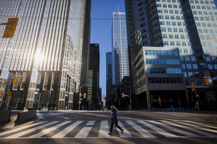 A woman crosses a street in Toronto's financial district.