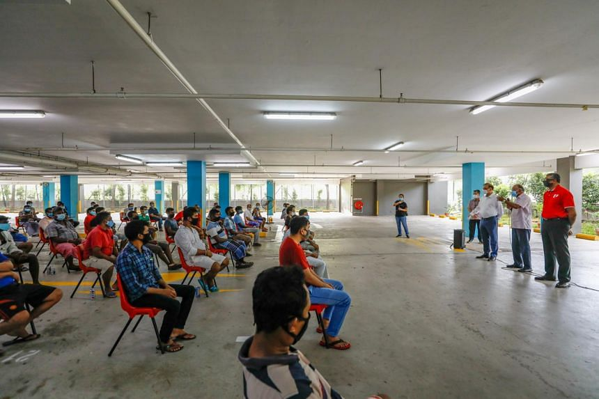 Minister for Home Affairs and Law K. Shanmugam (centre, at right) speaks to workers from the Westlite Papan dormitory on April 22, 2020.