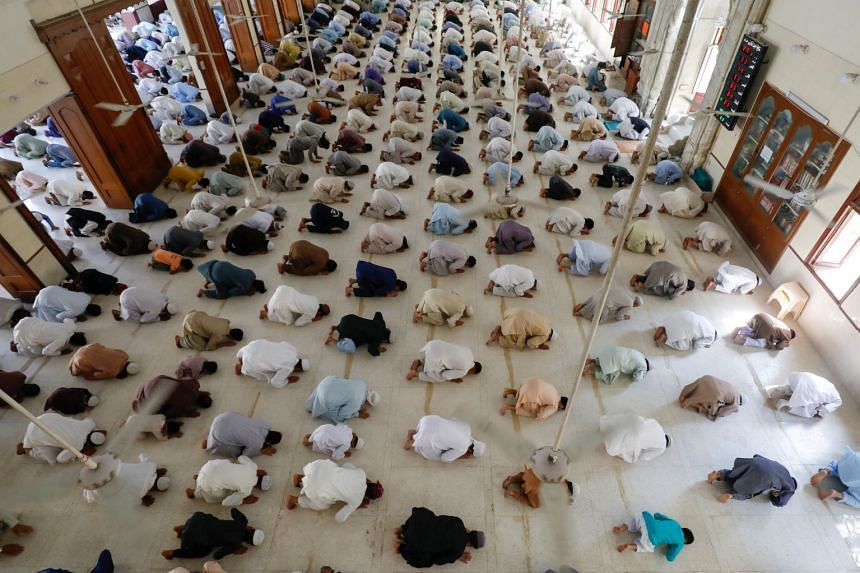 Muslims maintain safe distance as they attend Friday prayers in Karachi, April 17, 2020.