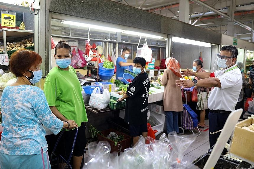 An SG Clean ambassador (right) ensuring shoppers at the wet market at Marsiling Lane adhere to safe distancing rules at around 10.20am yesterday. Despite it being an even date, meaning only shoppers whose NRIC number has an even last digit can enter,