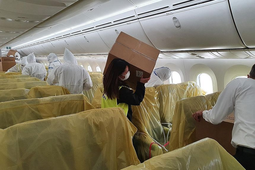 An SIA staff member with a box of medical supplies on board one of the carrier's passenger planes.