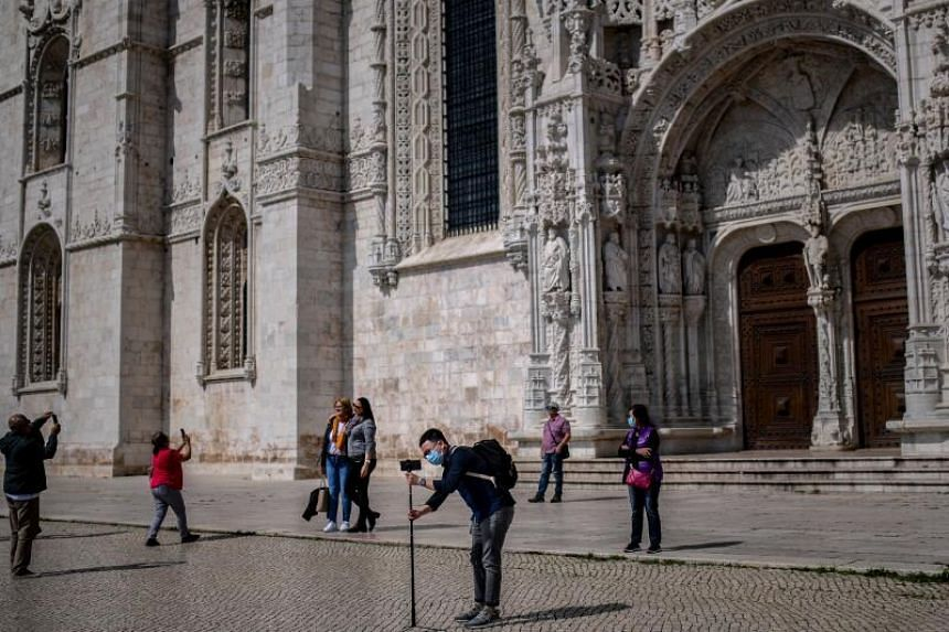 A tourist takes photos outside the Jeronimos Monastery in Lisbon on March 12, 2020.