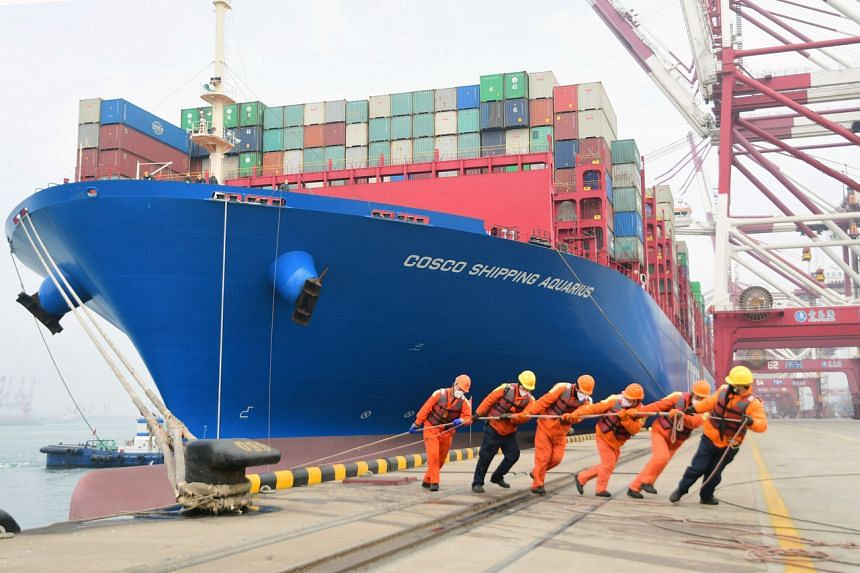 Workers wearing face masks rope a container ship at a port in Qingdao, Shandong province, China, on Feb 11, 2020.