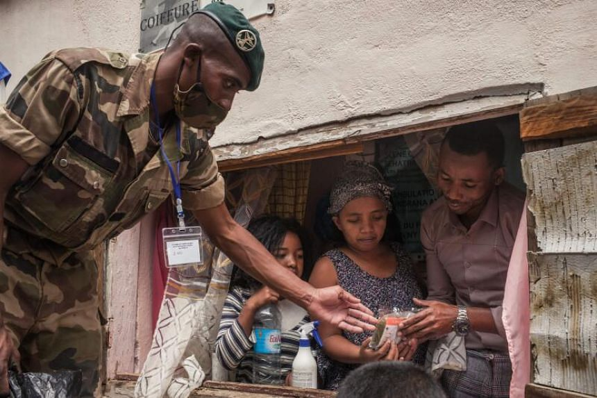 Madagascar soldiers distribute masks and herbal tea to people in the capital of Antananarivo on April 22, 2020.