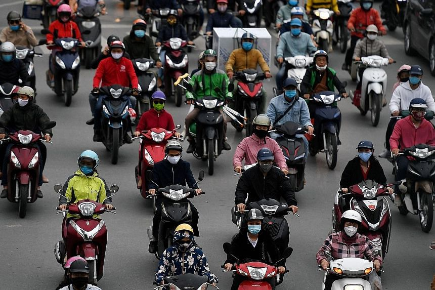Motorists in Hanoi yesterday. Vietnam has been under partial lockdown since the beginning of this month, but the government has said that some shops and services will be allowed to reopen.