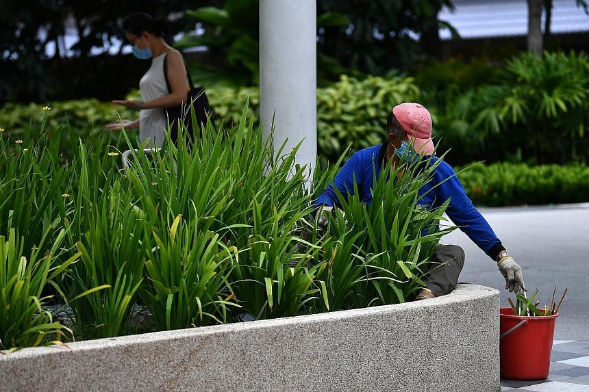 A landscape worker pruning plants outside Heartbeat @ Bedok yesterday. The cut in the number of essential services would reduce the proportion of the workforce commuting to work from 20 per cent to 15 per cent.
