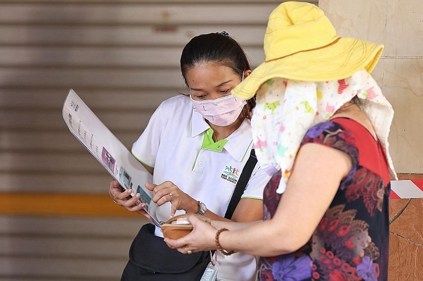 A staff member from Nee Soon Town Council explaining the stricter rules for entry at Chong Pang Market to a shopper yesterday.