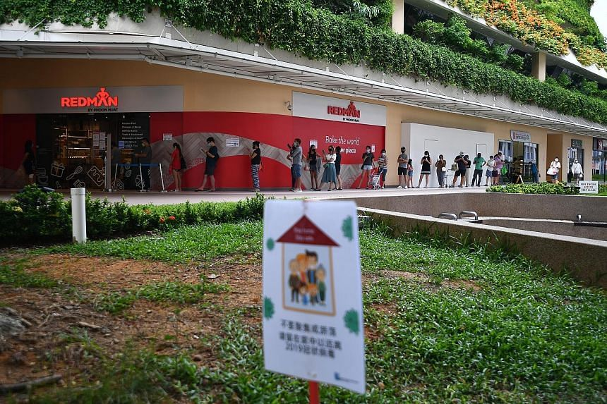 A long queue of shoppers waiting to enter a RedMan by Phoon Huat store at Heartbeat @ Bedok yesterday. The number of new cases in the general community has decreased, from an average of 34 cases a day in the week before, to an average of 25 a day in