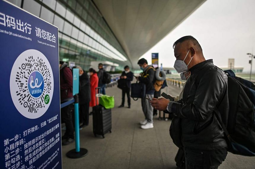 A passenger prepares to scan a Wuhan city health QR code in China on April 11, 2020.