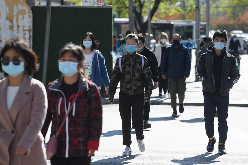 People wear face masks as they walk to a subway station in Beijing on April 23, 2020.