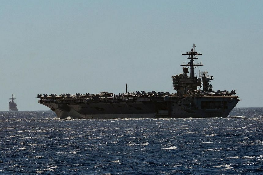 A photo from Feb 29, 2020, shows US vessels USS Theodore Roosevelt and USS Bunker Hill as they transit the Philippine Sea.