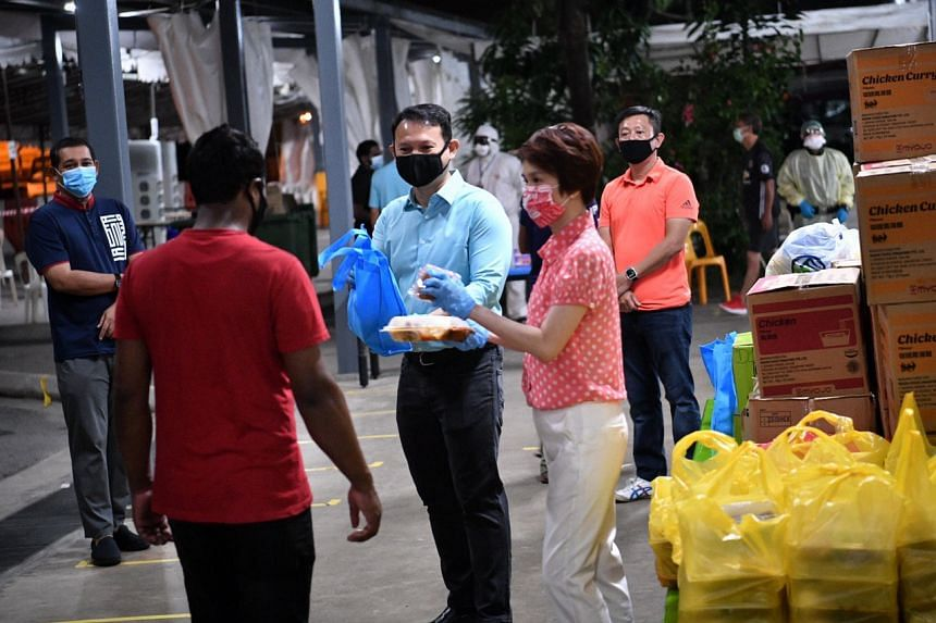 Minister of State for Manpower Zaqy Mohamad and Senior Parliamentary Secretary for Manpower Low Yen Ling giving out sahur (pre-dawn meal) to Muslim migrant workers at PPT Lodge 1A on April 24, 2020.