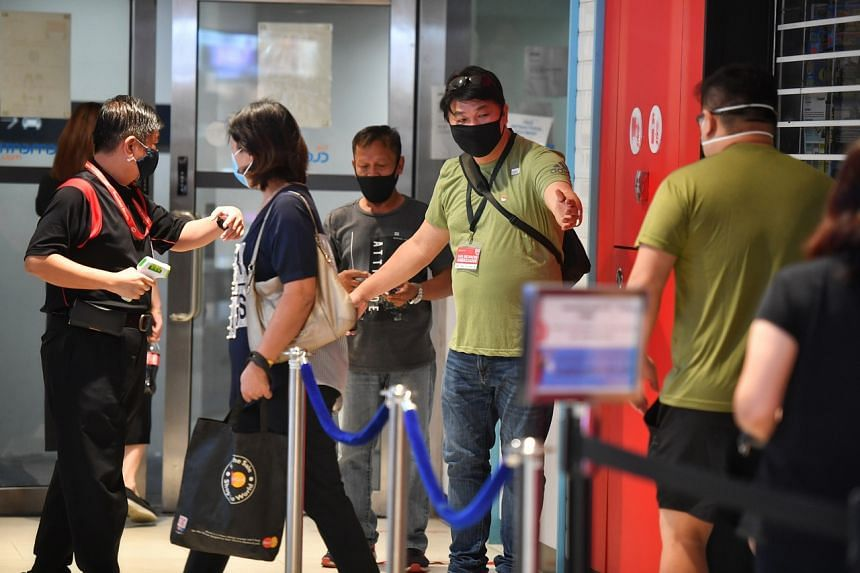 A safe distancing ambassador guides people queueing to enter Clementi Mall on April 22, 2020.