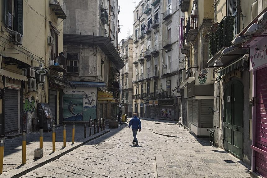 An empty market street in Naples, Italy, on April 12. The global economy is more likely to see a longer, U-shaped recovery after being pummelled into recession by the coronavirus pandemic, according to Reuters polls of economists from around the worl