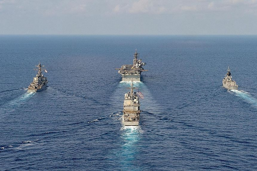 The Parramatta (top right) conducting manoeuvres in the South China Sea with the USS America (top centre), the USS Barry (top left) and the USS Bunker Hill, in this April 18 handout photo from the Australian Department of Defence. Commander Anita Nem