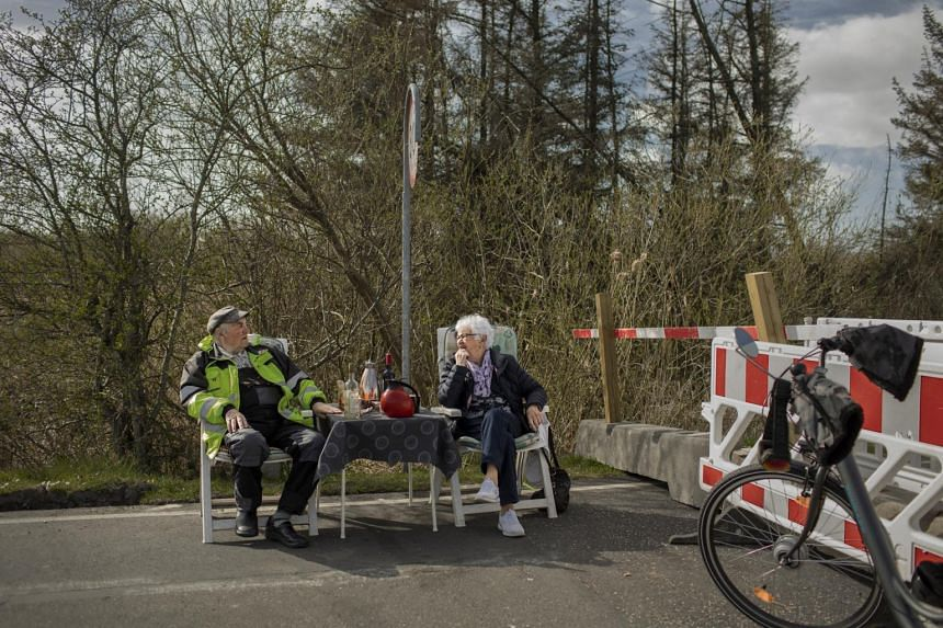 Karsten Tüchsen Hansen (left) and Inga Rasmussen meet at the Mollehusvej Border Crossing, between Denmark and Germany, on April 16, 2020.