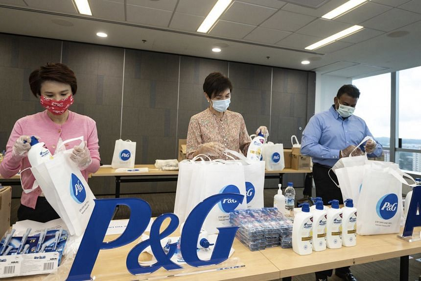 (From left) Senior Parliamentary Secretary for Manpower Low Yen Ling, Manpower Minister Josephine Teo and P&G's president for Asia-Pacific, Middle East and Africa Magesvaran Suranjan assembling the care packs.