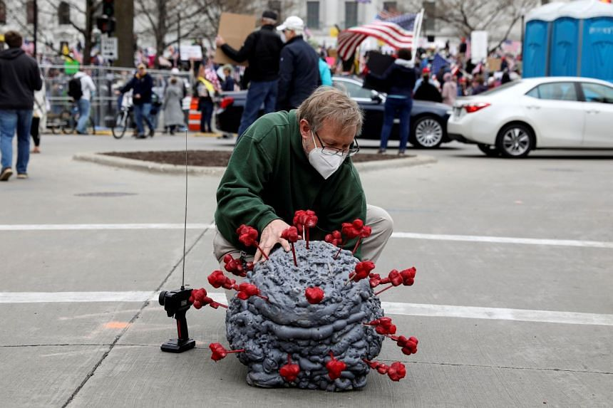 Tim Bailey of Wisconsin in the US prepares to drive a remote-controlled coronavirus model during a protest against the state's extended stay-at-home order.