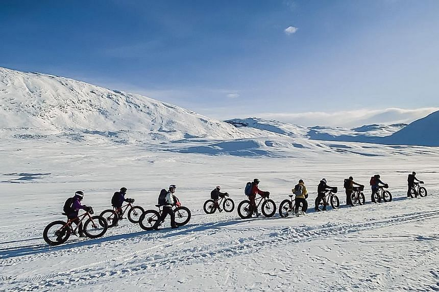 With soft snow on the trail, team members get off their fat bikes to push them instead.