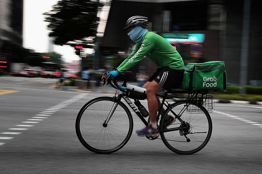 A GrabFood delivery partner in the city area earlier this month. With people staying in and more ordering food, it is not difficult for riders to make about 20 trips a day.
